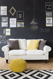 Sophisticated interior with motivational phrases. Sophisticated blackdesign interior with white comfortable sofa standing by a blackboard wall full of Royalty Free Stock Photo