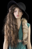 Sophisticated ladyportrait  with fur and hat. Sophisticated elegant woman portrait with hair style and wearing a green dress and a tail fur , black hat Royalty Free Stock Photo