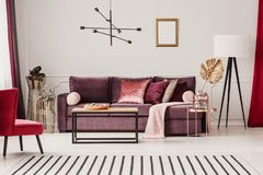 Sophisticated living room interior. Gold leaf on copper table in sophisticated living room interior with striped carpet and violet sofa Royalty Free Stock Photo