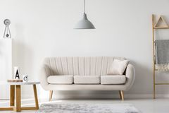 Sophisticated living room interior. Gray lamp above beige couch in sophisticated living room interior with ladder and wooden round table Stock Photos