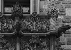 Sophisticated lizards on the balcony. Shot in black and white detail of the sculpture on the facade of this historic building representing some characters / stock image