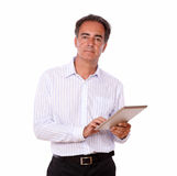 Sophisticated man using his tablet pc. Portrait of a sophisticated man using his tablet pc while standing and looking at you on isolated studio Royalty Free Stock Images