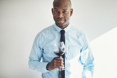 Sophisticated mature man drinking a glass of red wine. Sophisticated mature African man in a shirt and tie drinking a glass of red wine stock image