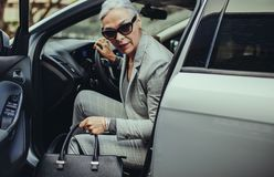 Sophisticated mature woman disembarking the car. Senior businesswoman with purse getting out of her car. Sophisticated mature woman disembarking the car stock image