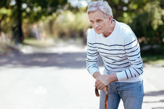 Sophisticated old man enjoying spring in the park. Feeling depressed. Involved thoughtful old man looking away and leaning on the stick while walking in the park Stock Photography