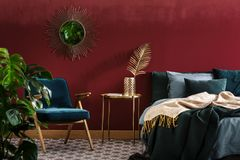 Sophisticated red bedroom with mirror. Gold table between green armchair and bed in sophisticated red bedroom interior with mirror Royalty Free Stock Images