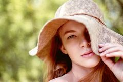 A sophisticated red-haired girl in a simple linen dress, in a light wide-brimmed hat.Model look. Natural beauty. A sophisticated red-haired girl in a simple royalty free stock photos