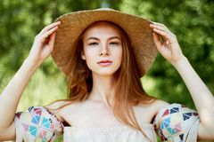 A sophisticated red-haired girl in a simple linen dress, in a light wide-brimmed hat.Model look. Natural beauty. A sophisticated red-haired girl in a simple royalty free stock image
