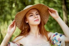 A sophisticated red-haired girl in a simple linen dress, in a light wide-brimmed hat.Model look. Natural beauty. A sophisticated red-haired girl in a simple stock photography