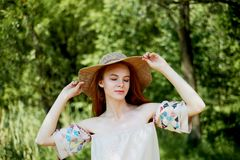 A sophisticated red-haired girl in a simple linen dress, in a light wide-brimmed hat.Model look. Natural beauty. A sophisticated red-haired girl in a simple stock photo