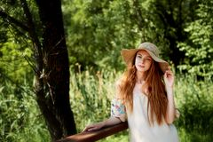 A sophisticated red-haired girl in a simple linen dress, in a light wide-brimmed hat.Model look. Natural beauty. A sophisticated red-haired girl in a simple royalty free stock photo
