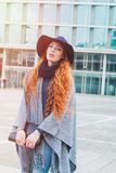 Sophisticated red headed woman wearing floppy hat. Sophisticated red headed woman wearing floppy blue hat and grey poncho poses near modern office building Stock Images