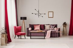 Sophisticated red living room. Lamp above table in sophisticated living room interior with red armchair and violet sofa against the wall with a poster stock image