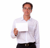 Sophisticated senior man holding a blank card. Portrait of a sophisticated senior man holding a blank card while standing and looking at you on isolated Royalty Free Stock Photos