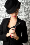 Sophisticated woman. Holding a gun in her hands Royalty Free Stock Photography