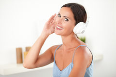 Sophisticated woman with headphones looking happy. Sophisticated woman in blue shirt with headphones looking happy in her room Stock Photo