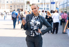 Sophisticated woman with mobile phone. In the street Stock Photo
