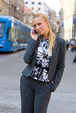 Sophisticated woman with mobile phone. In the street Royalty Free Stock Image