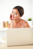 Sophisticated woman working on her laptop. Sophisticated woman in blue blouse working on her laptop in her house Stock Photos
