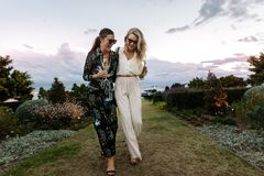 Sophisticated women walking outdoors with wine. Full length of fashionable women walking together and laughing outdoors. Females friends with a glass of wine stock photo