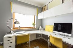 Sophisticated workspace with designer lamp. Monitor on desk in sophisticated workspace with designer lamp and yellow chairs Royalty Free Stock Photography