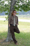Sophisticated Young Man. A sophisticated, professional young man leans against a tree Royalty Free Stock Images