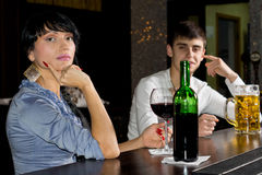 Sophisticated young woman drinking at a bar. Sophisticated young women drinking at a bar enjoying a bottle of red wine turning to look at the camera with a men Stock Image