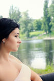 Sophisticated young woman overlooking a lake. Sophisticated young woman sitting overlooking a lake staring ahead with a thoughtful expression as she relaxes Royalty Free Stock Photos