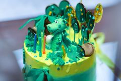 Sophisticatedly designed homemade Birthday cake with Dinosaur figure between the sweeties, green and yellow colors. stock photo