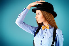 Sophistication. Elegant girl model poses in blouse, bow tie and bowler hat. Refined style of old Europe stock photography