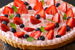 Sophistication tart with strawberries and blueberries with whipp. Ed cream close-up on the table. horizontal stock photo