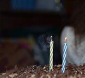 Sopló hacia fuera las llamas de las velas en el ¿de Ð-аÐ'уД и Ð de la torta Fotografía de archivo
