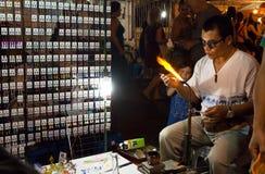 Soplador de vidrio que hace los nuevos productos de cristal para la venta durante mercado de la noche Foto de archivo libre de regalías