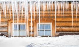 Sople i śnieg na starej drewnianej chałupie zdjęcie stock