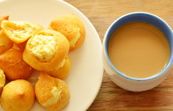 Soplo poner crema de la vainilla en la taza del plato y de café Fotos de archivo