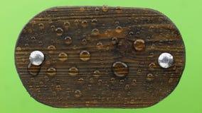 Soplos del viento en las gotas de agua en un tablero de madera oscuro con los pernos del hierro Aislado en fondo verde almacen de video