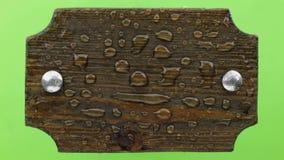 Soplos del viento en las gotas de agua en un tablero de madera oscuro con los pernos del hierro Aislado en fondo verde metrajes