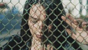 Soplos en la cerca de la malla con las manos para mujer La muchacha enojada bate las manos en una cerca de la rejilla almacen de video