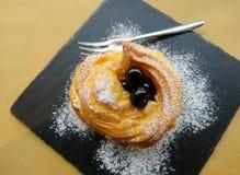Soplos poner crema con crema y cerezas en jarabe Imagen de archivo libre de regalías