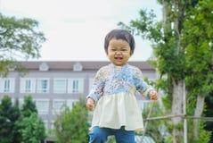 Soporte asiático feliz de la muchacha del primer en piso de la hierba en el fondo del jardín con el movimiento de la diversión fotos de archivo