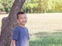 Soporte asiático lindo del muchacho del preadolescente en un parque público Imagen de archivo libre de regalías