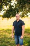 Soporte atractivo del individuo cerca de un árbol verde grande Historia de amor fotos de archivo libres de regalías