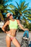Soporte bastante atractivo de la mujer joven con longboard delante de las palmas en tiempo soleado Hembra sonriente Ocio Fotografía de archivo libre de regalías