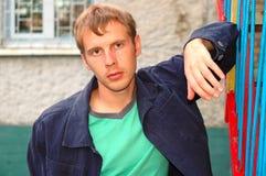Soporte con estilo joven del hombre cerca de la barandilla. Foto de archivo libre de regalías