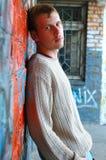 Soporte con estilo joven del hombre cerca de la pared de ladrillo de la pintada. Fotografía de archivo