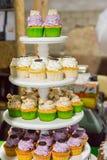 Soporte con gradas de la torta con las magdalenas coloridas Foto de archivo libre de regalías