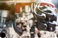 Soporte de cuatro cilindros del motor de la bobina del cierre del alambre ascendente del distribuidor en el coche con luz del sol fotos de archivo