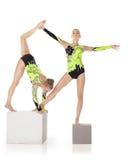 Soporte de dos acróbatas de la alta habilidad en el cubo Fotografía de archivo libre de regalías