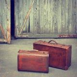Soporte de dos maletas que viaja cerca de un garaje Fotos de archivo libres de regalías