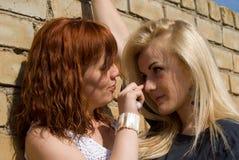 Soporte de dos muchachas en la pared Fotografía de archivo libre de regalías